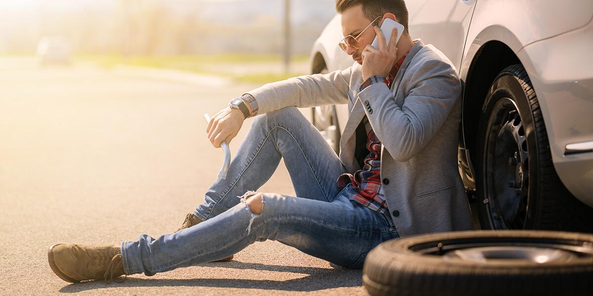 employee fixing flat tire on personal vehicle